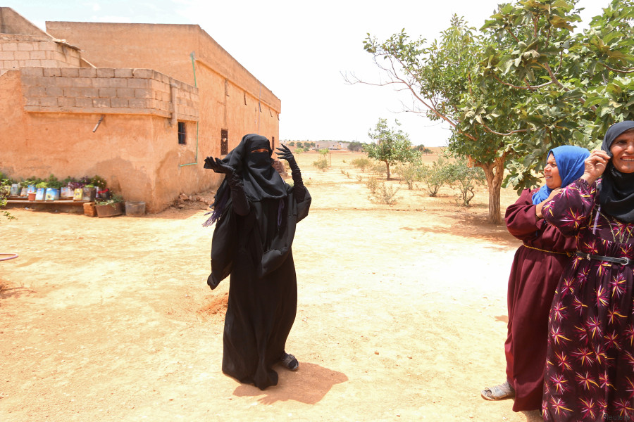 A woman in a Niqab stands in her village after Syria Democratic Forces (SDF) took control of it, on the outskirts of Manbij city